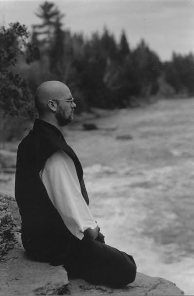 Ven. Anzan Hoshin roshi sittin zazen on a rock in front of a rapid river, 1988, Photograph by the late Ven. Shikai Zuiko O-sensei