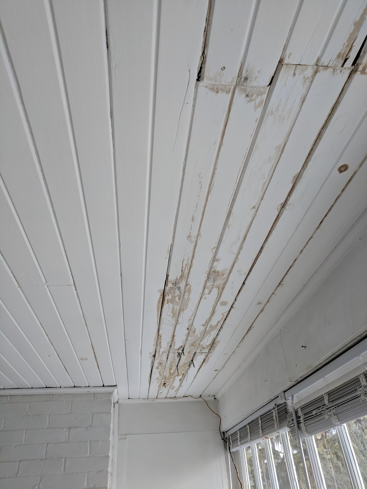 Covered balcony ceiling showing areas of frequent leaks.