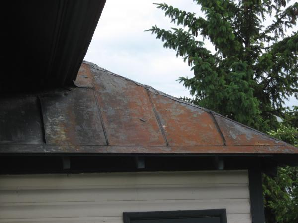 Roof of covered balcony on west side of building showing rusting metal surface and patched seams