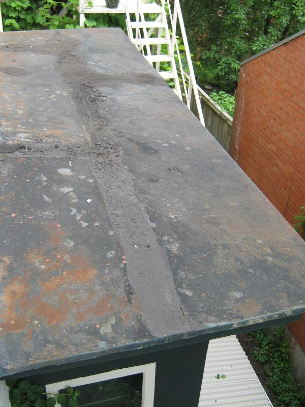 Roof of first-floor library bay window showing past patching and rusting metal surface