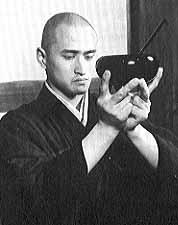 Monk holding up an oryoki bowl