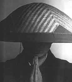 Monk with hands in gassho wearing a begging hat