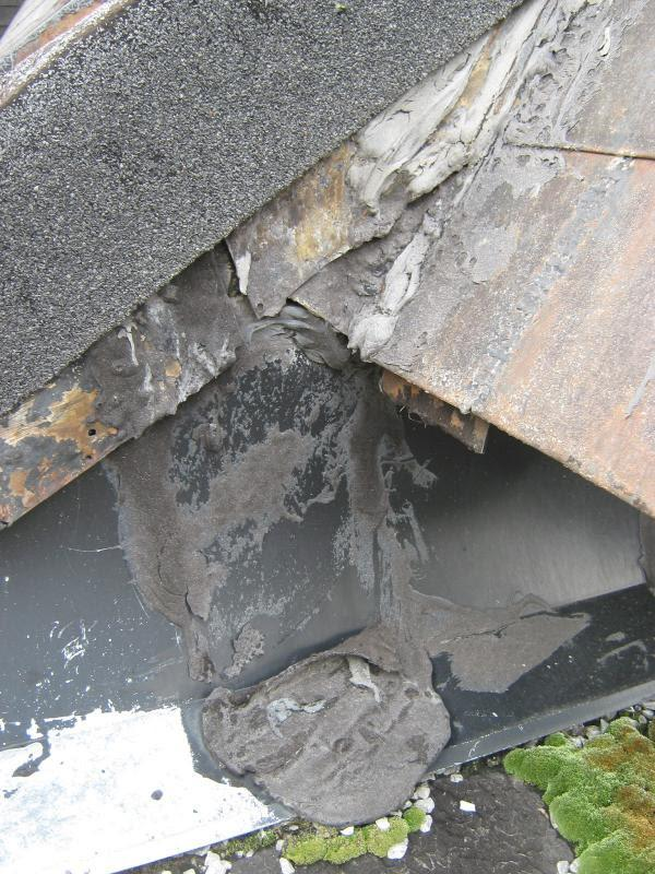 Detail of Osho-ryo roof showing failing flashing and past patching; green is moss growing on gravel roof surface