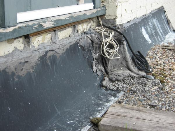 Detail of Osho-ryo roof showing flashing in poor repair, unsecured wires, and the deterioration of the old tar and gravel covering